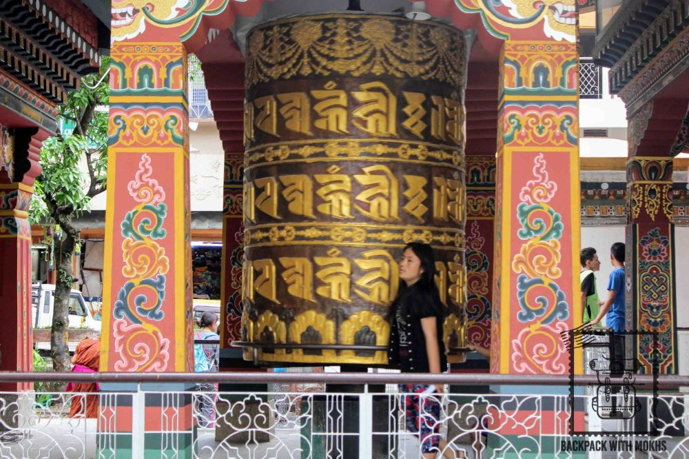 Prayer wheel being rotated by a woman in a temple