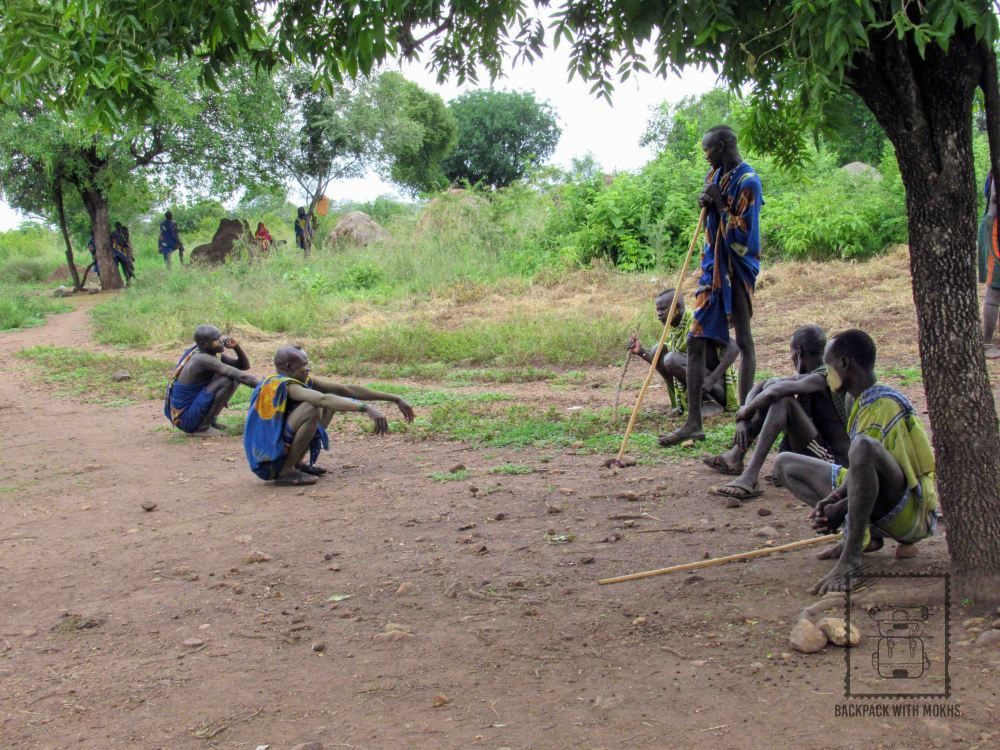 Mursi men sitting on the ground together